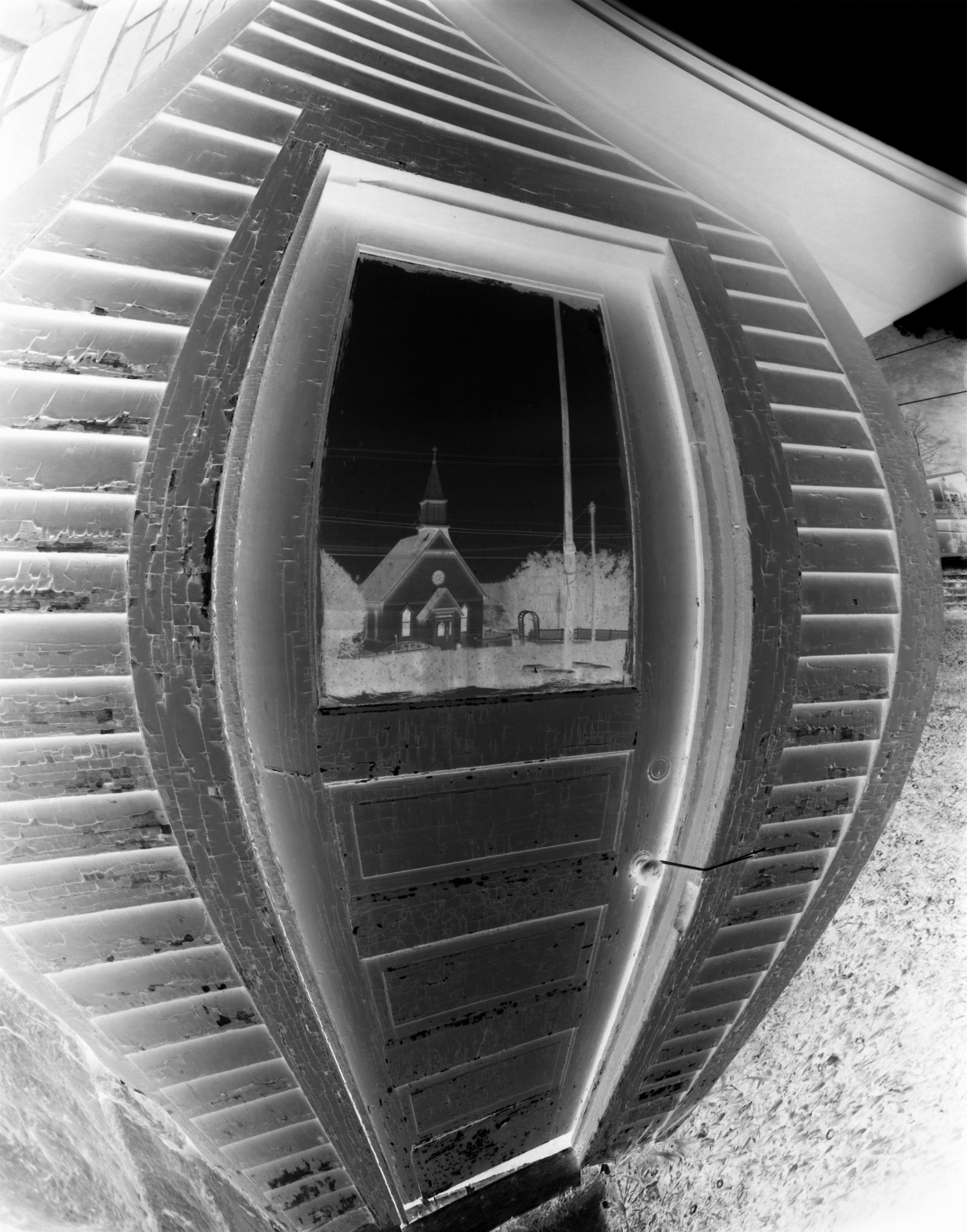 Homer United Methodist Church reflected in a window of the Homer township hall.